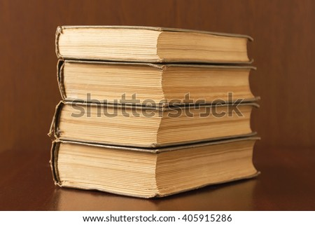 Four old books stacked on a table - stock photo