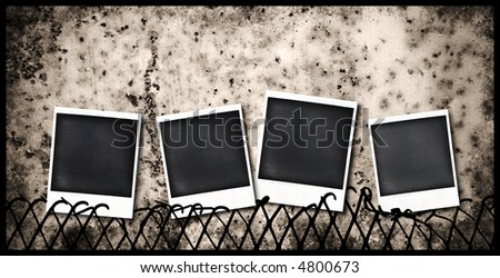 four old  instant photo frames stuck to a fence - stock photo