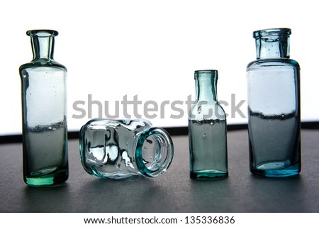 four old medical green and blue glass jars on a white-grey background - stock photo