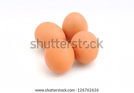 Four organic brown eggs on white background