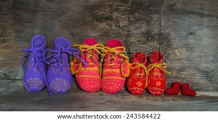 four pairs of children's  felted  shoes on the wooden background - stock photo