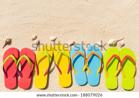 Four pairs of flip flops in a row on beach - stock photo