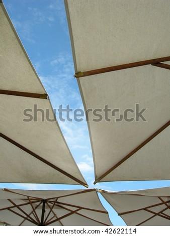 Four parasols building a cross of blue sky. - stock photo