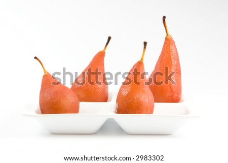 Four pears pouched in red wine lying in the white tray with dividers - stock photo