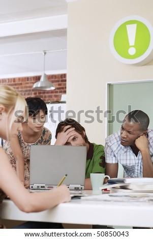 Four people having meeting around laptop. - stock photo