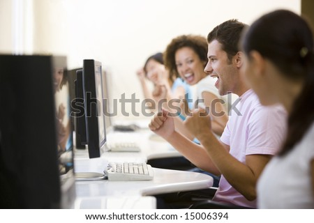 Four people in computer room cheering and smiling