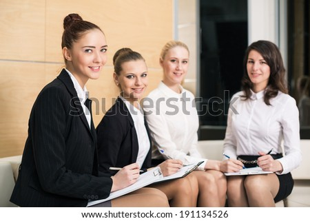 Four people in lobby writing at clipboard smiling