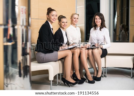 Four people in lobby writing at clipboard smiling - stock photo