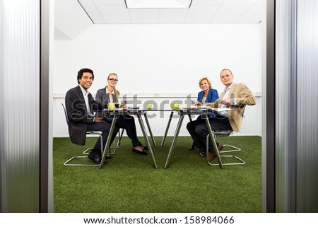 Four people meeting in a green, sustainable, conference room - stock photo