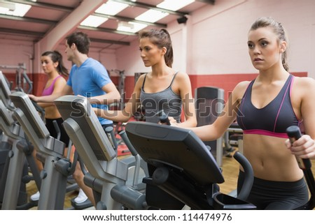 Four people on step machines in gym