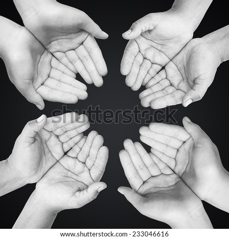 Four people open empty hands with palms up over black background. International Volunteers Day, International Human Solidarity Day concept. - stock photo