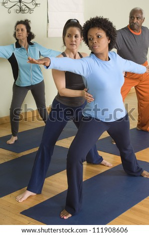 Four people practicing yoga - stock photo