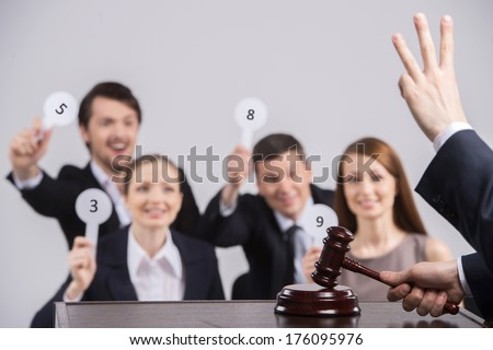 four people raising cards with number. judge counting and holding hammer in hands - stock photo