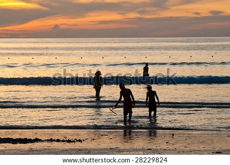 four people silhouettes on the Patong beach, Phuket, Thailand