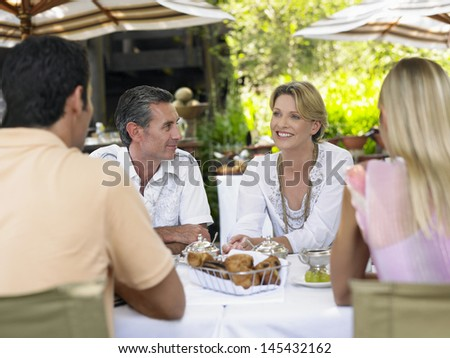 Four people sitting at outdoor dining table and talking - stock photo