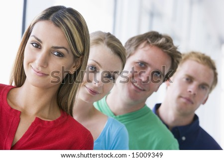 Four people standing in corridor smiling - stock photo