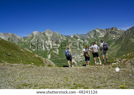 Four persons watching around on a mountain