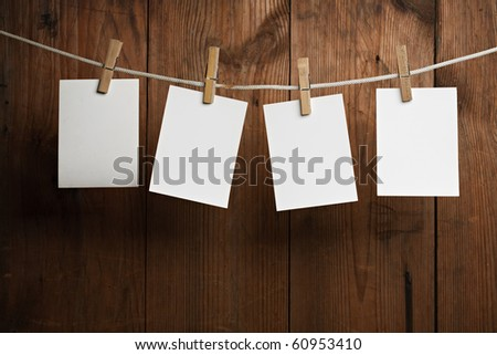 four photo paper attach to rope with clothes pins on wooden background