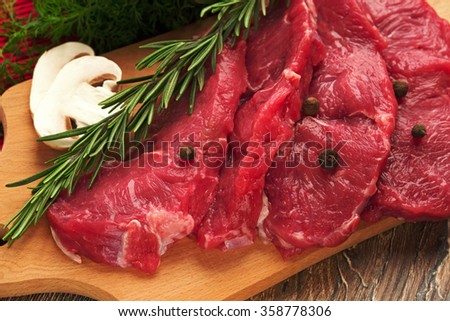 four piece of fresh, raw, juicy meat of veal or stake of beef, on a kitchen table on a wooden chopping board with  black pepper, fresh green onions,the fresh  mushrooms, fennel, rosemary  - stock photo