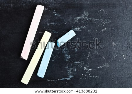 four pieces of chalk over a blackboard