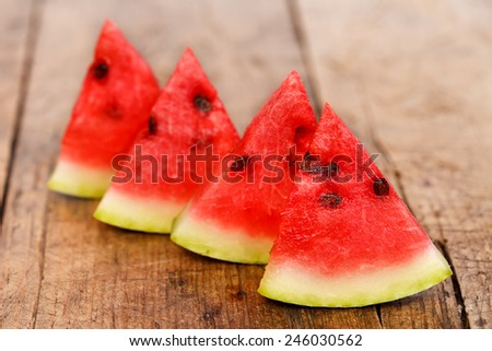 Four pieces of fresh watermelon on rustic wooden table