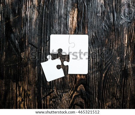 four pieces of white jigsaw on dark wooden table