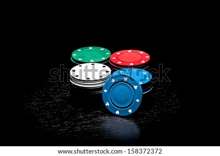 four piles of colorful fiches on black wood table - stock photo