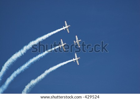 Four planes fly in formation with vapor trails - stock photo