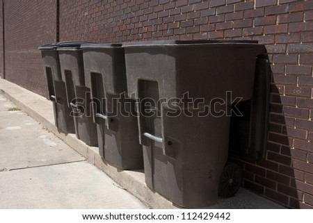 Four plastic trash dumpsers in an alley