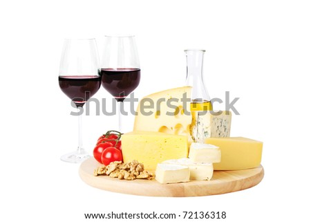 Four popular kinds of cheese, tomatoes, olive oil and two glasses of red wine on a white background. A shot horizontal, focus in the shot foreground. - stock photo