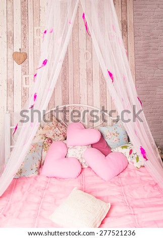 Four-poster bed with pink pillows in the studio - stock photo