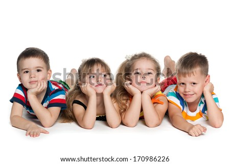 Four preschool children are lying on the floor on the white background