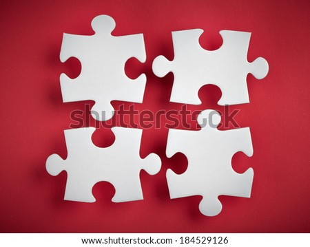 four puzzle pieces on red background - stock photo