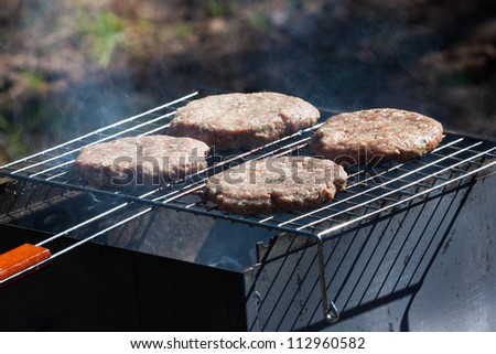 Four raw Hamburgers on Barbeque Grill with smoke - stock photo