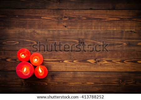 Four red candles on brown wooden table, top view - stock photo