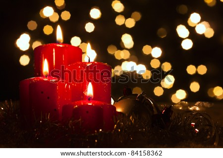 four red candles with christmas balls in atmospheric light - stock photo