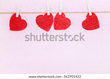 Four red hearts hanging on rope on white clothespins. Postcard for lovers day - stock photo