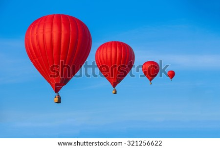 Four Red hot air balloons in blue sky with white clouds - stock photo