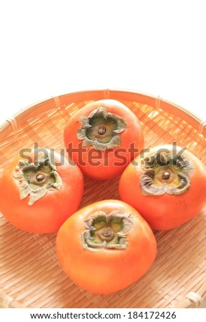 Four red persimmons sitting on a straw plate. - stock photo
