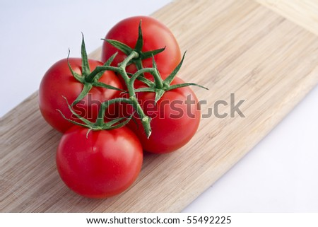 Four Red Tomatoes on Cutting Board