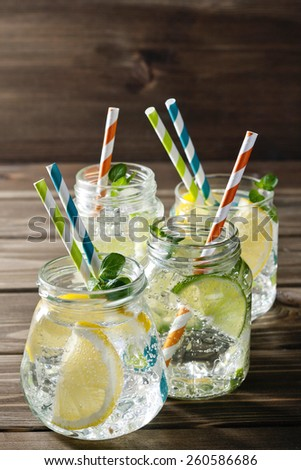 Four refreshing cocktails in mason jars over wooden background - stock photo