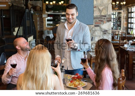 Four relaxed people sitting at restaurant table - stock photo