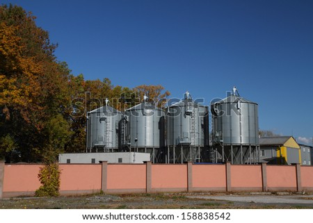 Four reservoirs for liquid chemicals with blue sky. - stock photo