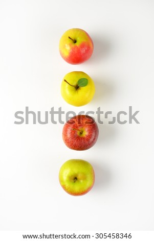 four ripe apples in a row on white background - stock photo
