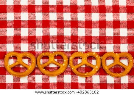 Four salted pretzels on the red white checkered tablecloth background, selective focus - stock photo