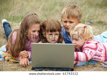 four schoolchild lying on green meadows and exercise on a laptop - stock photo