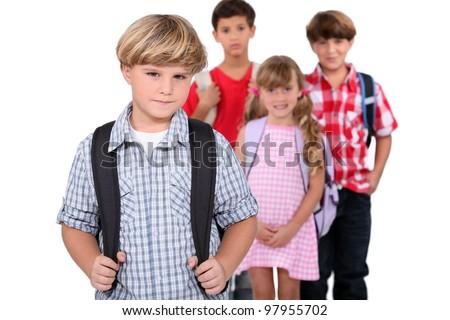 Four schoolchildren with backpacks - stock photo