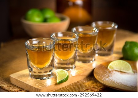 Four shot glasses with tequila bottle and bowl of limes with salt at a bar - stock photo