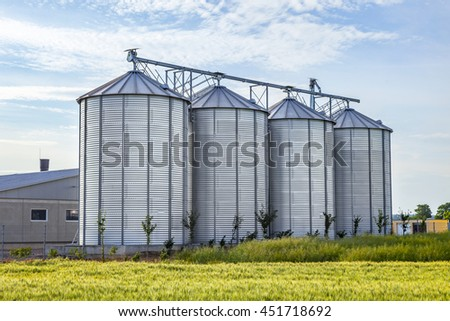 four silver silos in corn field with clouds - stock photo
