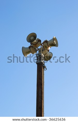 Four sirens on a pole with blue sky in the background. - stock photo